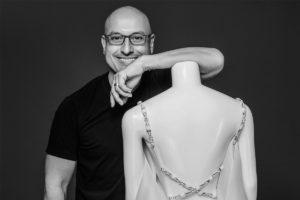 Portrait of designer Angel Sanchez leaning on a dressform